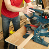 Mark Powers uses a miter saw to cut pieces for a dog crate