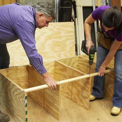 Tom Silva and Amy Paladino install the rail for the tool bench outer frame