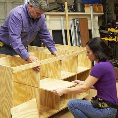 Tom Silva and Amy Paladino sliding shelves into the tool bench