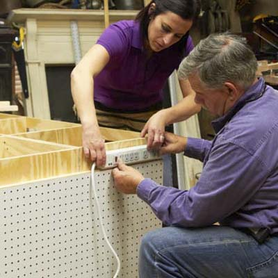 Tom Silva and Amy Paladino mount a power strip to the side of the tool bench
