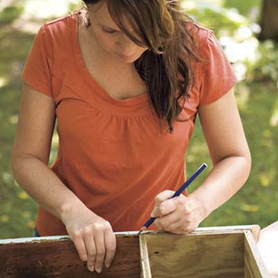 woman measuring window box frame