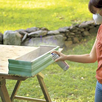 woman sealing window box finish