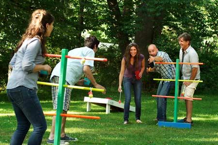 men and women playing ladder golf yard game