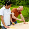 two men tracing circle for cornhole game board