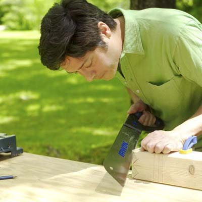 man using pull saw to make king crown for yard game of kubb