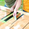 people removing the tape used to mask the lines while building a ricochet game board