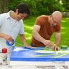 two men taping off design for cornhole game board
