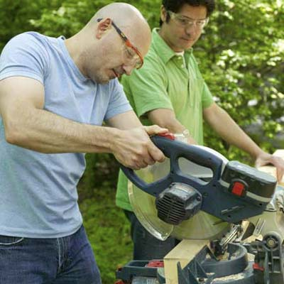 men using miter saw to cut kubb pieces