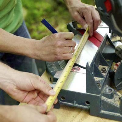 men measuring dowels for kubb game