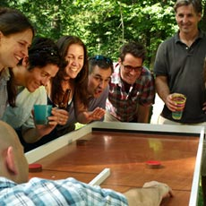 group of happy people standing around a team saturday ricochet game board