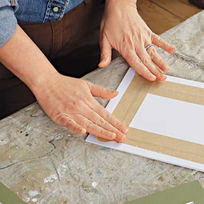 woman secures the photos to the back of mat with paper tape