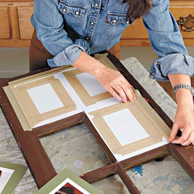 woman arranges the matted photos to the back side of the window