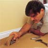 person using a carpet-edging tool to demonstrate how-to install carpet