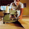 person finishing the edges to demonstrate how-to install carpet