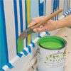 using a brush to cut in the stripes between arrows to paint a striped wall