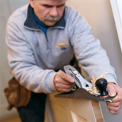 this old house general contractor tom silva using a hand plane to fix a stuck door