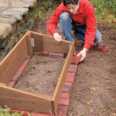 installing pavers around the the cold frame area as a stable foundation