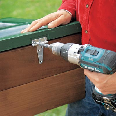fastening the lid to the cold frame with a drill/driver