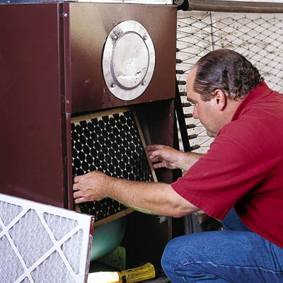 man replacing air filter of furnace, easy diy new year's resolutions