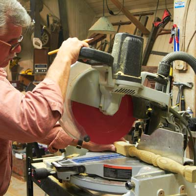 Tom Silva uses a miter saw to cut spindles to length