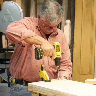 Tom Silva drills holes in the shelves