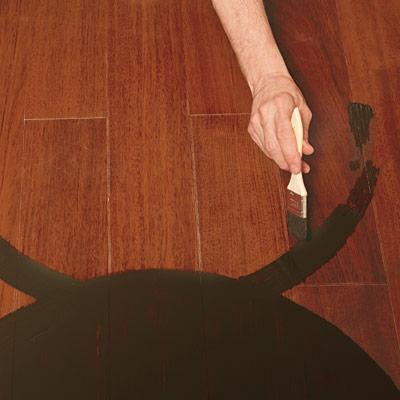 hand painting medallion design on wood floor