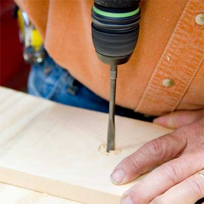 hands drilling a pilot hole