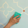 man using sponge to erase chalk line after painting wall design