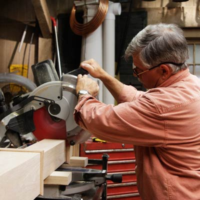 Tom Silva cuts the leg for a trestle table with a miter saw