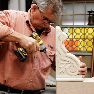Tom Silva attaches the corbel for a trestle table to the base of the table leg