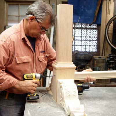 Tom Silva attaches the stretcher for a trestle table to the table leg