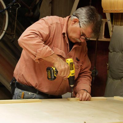 Tom Silva attaches cleats to the underside of the table top for a trestle table with a drill/driver