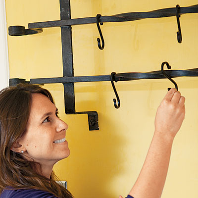 Amy Hughes puts S-hooks on a newly installed pot rack