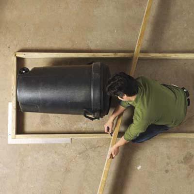 Mark Powers checking the size of his trash shed's framing using a 32-gallon trash can