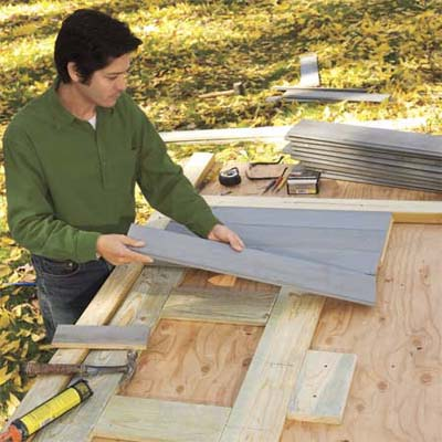 Mark Powers laying out siding before constructing the doors and lids of his trash shed