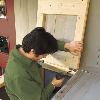 Mark Powers fastening a lid to the top of his trash shed