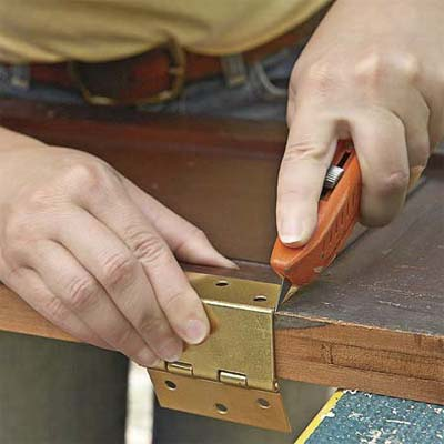 new mortices are cut to attach the new hardward where it will fit the shutter's new use as doors