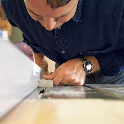 man roughing out profile of custom molding