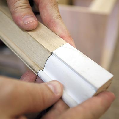 man checking new molding against original molding