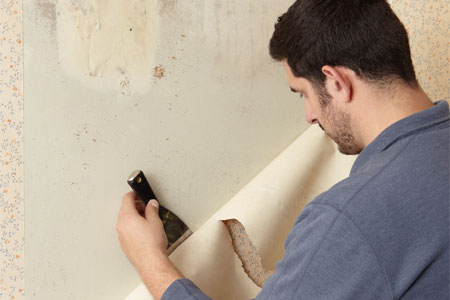Sal Vaglica stripping wallpaper with a putty knife