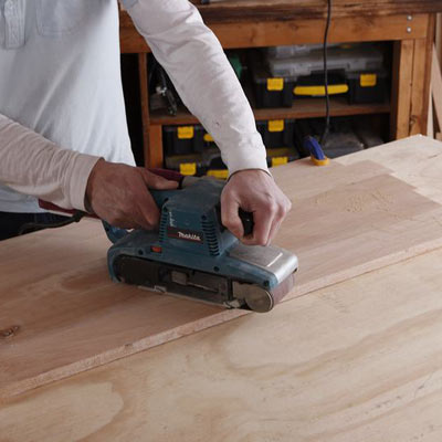 sanding the side of a storage chest with a belt sander