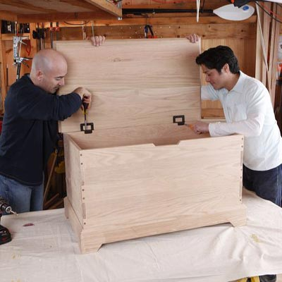 attaching the hinges to the lid of the storage chest