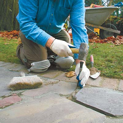 chiseling out the crumbling mortar in a cracked stone walkway