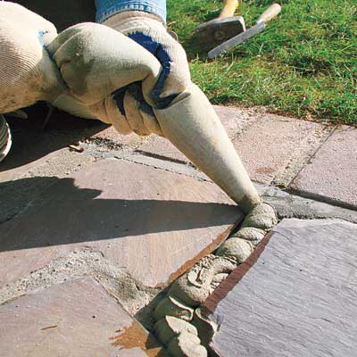 filling the joints in a stone walkway with fresh mortar