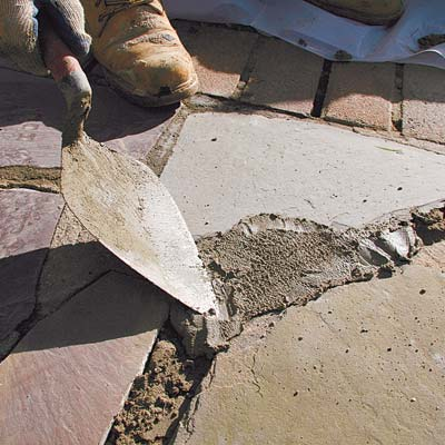 troweling the fresh mortar into joints in a stone walkway