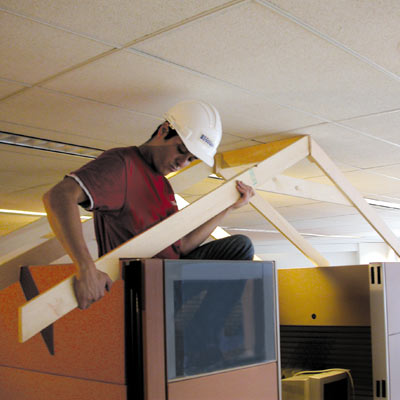 Mark Powers assembles a roof frame over an office cubicle