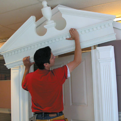 Mark Powers installs a pediment over an office cubicle
