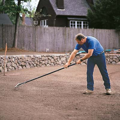 Roger Cook rakes the soil to level the surface