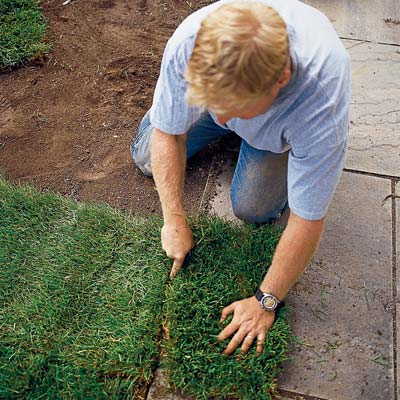 cutting the edge of sod with a knife along a paved walkway