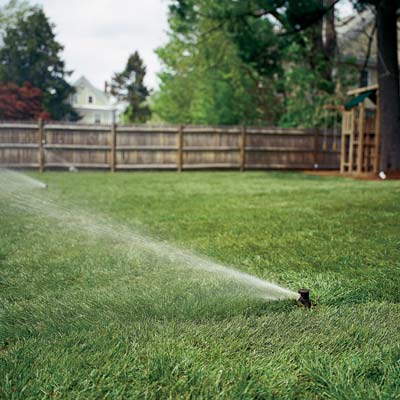 a sprinkler system waters a lawn